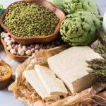 Varias fuentes de proteina vegetal, tofu tempe legumbres garbanzos judias lentejas soya cacahuetes frutos secos como nueces almendras anacardos pistachos pipas de calabaza semillas como el cañamo chia lino